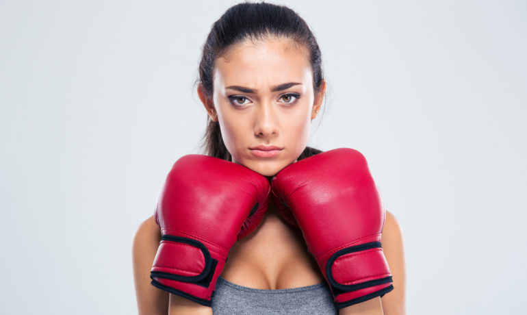 Portrait of a sports woman standing in defence stance with boxing gloves isolated on a white background