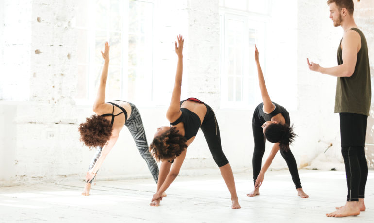 Group of young healthy women doing yoga under the guidance of a coach in gym